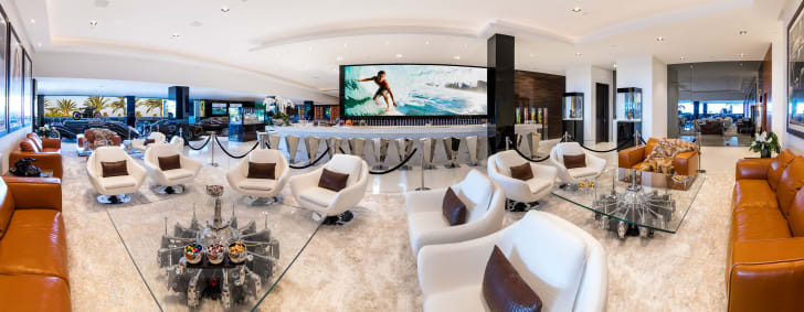 A lounge filled with white leather chairs with a full bar and large TV screen