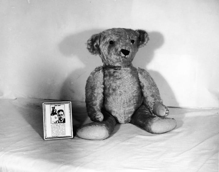 Still life of a 'Teddy' Bear sitting with its tag describing the origin of the toy and US president Theodore Roosevelt circa the 1950s.