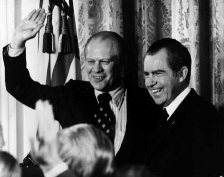 Gerald Fold waves while standing next to Richard Nixon