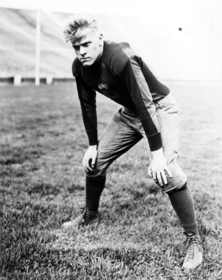 A young Gerald Ford poses while wearing his football uniform