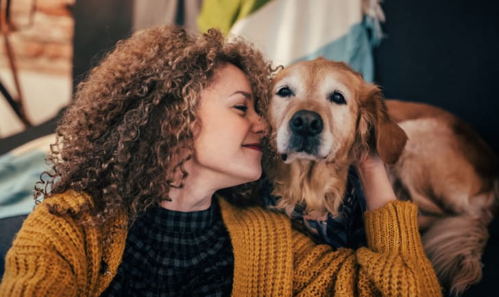 Woman cuddling her dog.