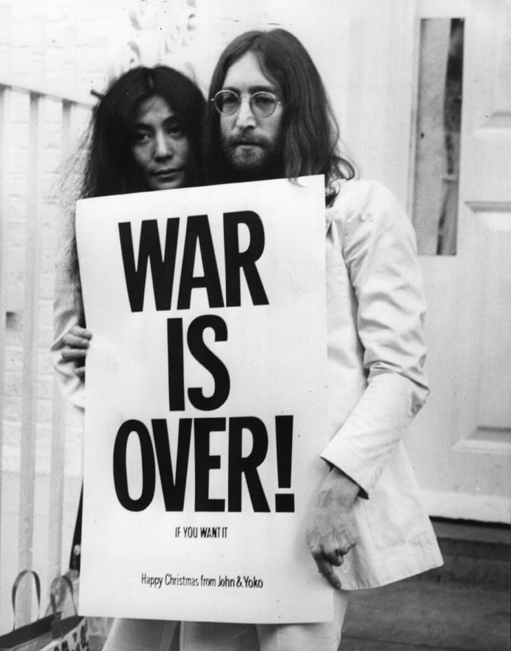 "John and Yoko hold up a protest sign that says ""War is over if you want it."""