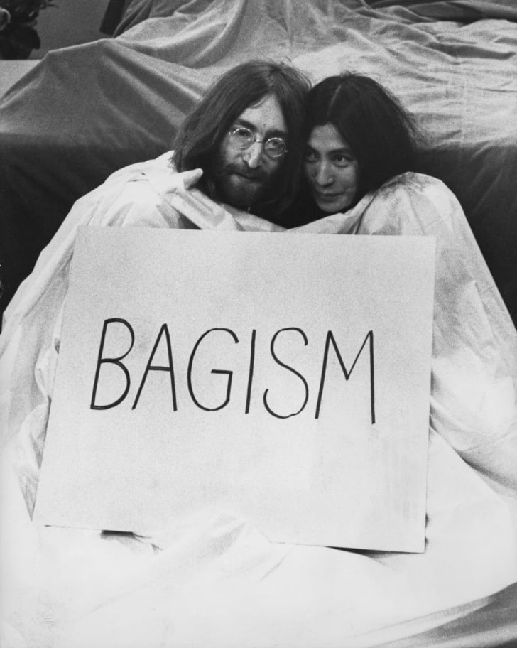 "John Lennon and Yoko Ono with a sign reading ""bagism"""