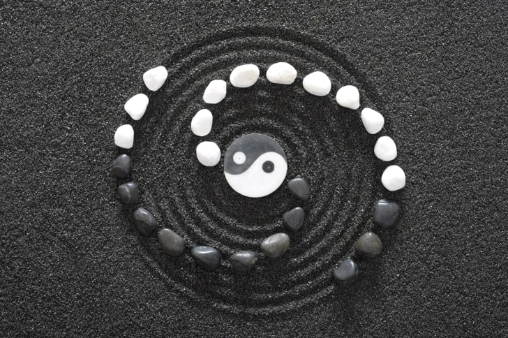 Yin and yang symbol on textured sand.