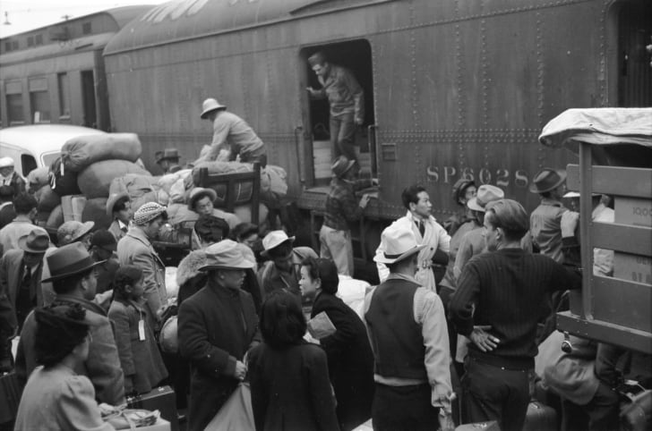 Japanese Americans going to Manzanar gather around a baggage car at the old Santa Fe Station. (April 1942)
