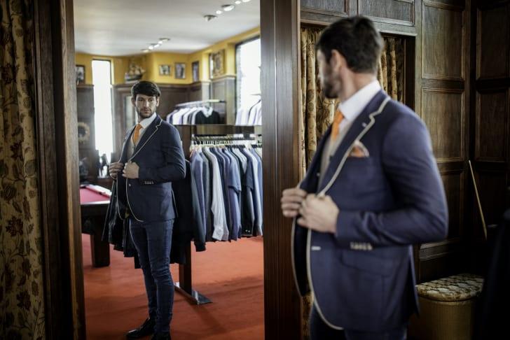 A man admiring himself in a mirror in a menswear shop