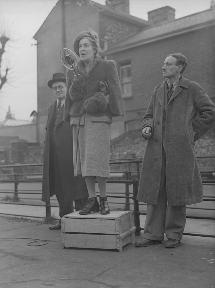 1944: A woman standing on a soapbox speaking into a mic