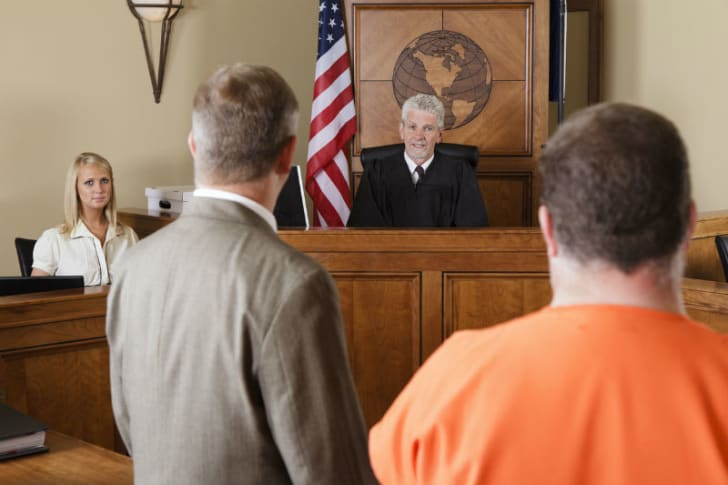 A criminal defense attorney stands near his client