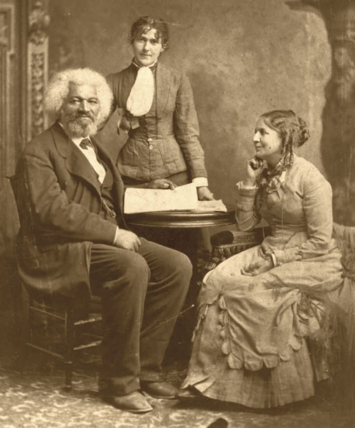 Frederick Douglass with Helen Pitts Douglass (seated, right) and her sister Eva Pitts (standing, center), circa the 1880s.