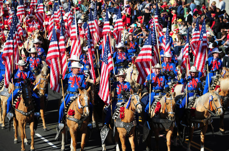 Participants on horseback hold U.S. flags during the annual Tournament of Roses Parade in Pasadena