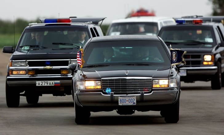 The presidential motorcade shows the proper flag placement for the front of a car.