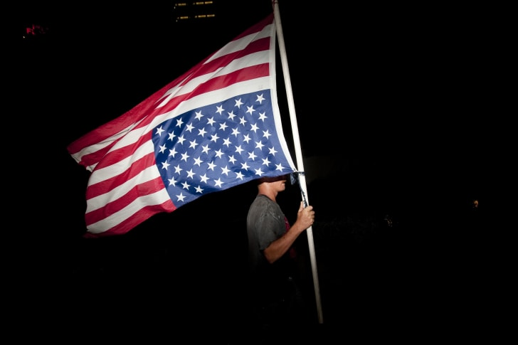 A protester marches with an upside-down American flag.