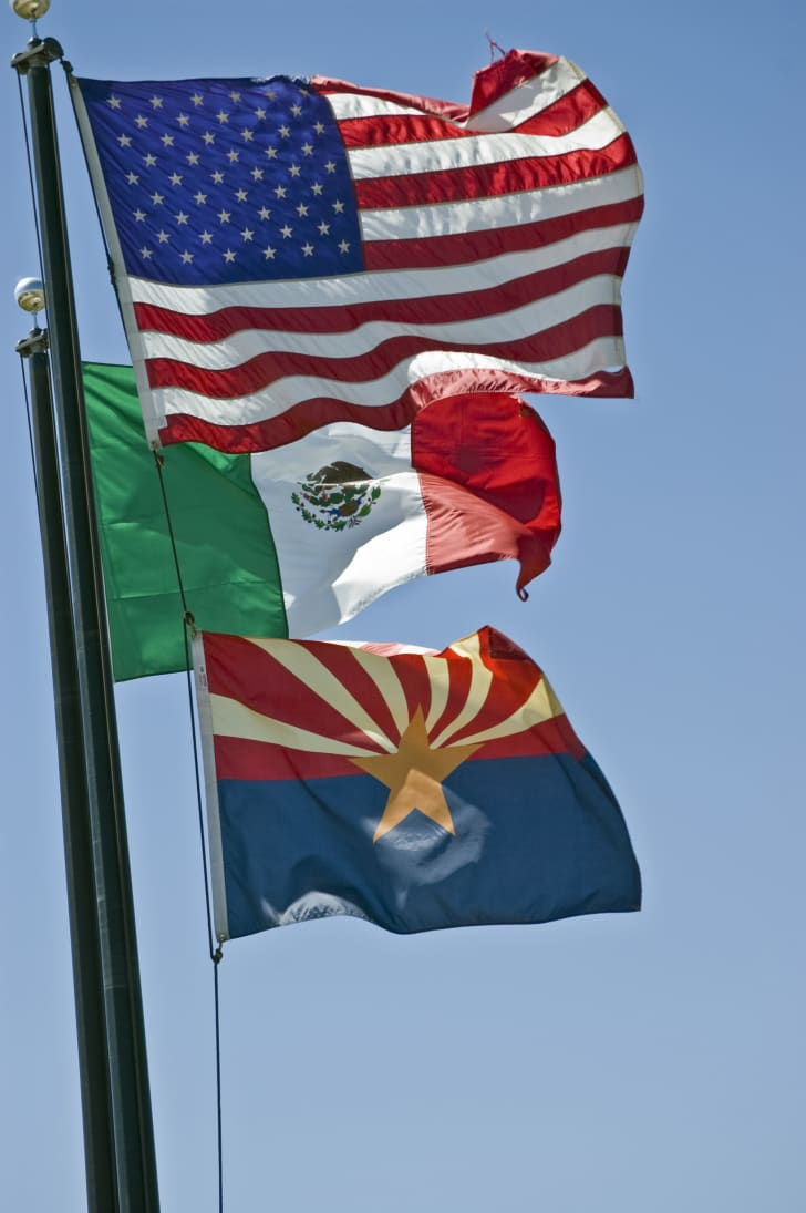 The American, Mexican, and Arizona flags hanging on poles.