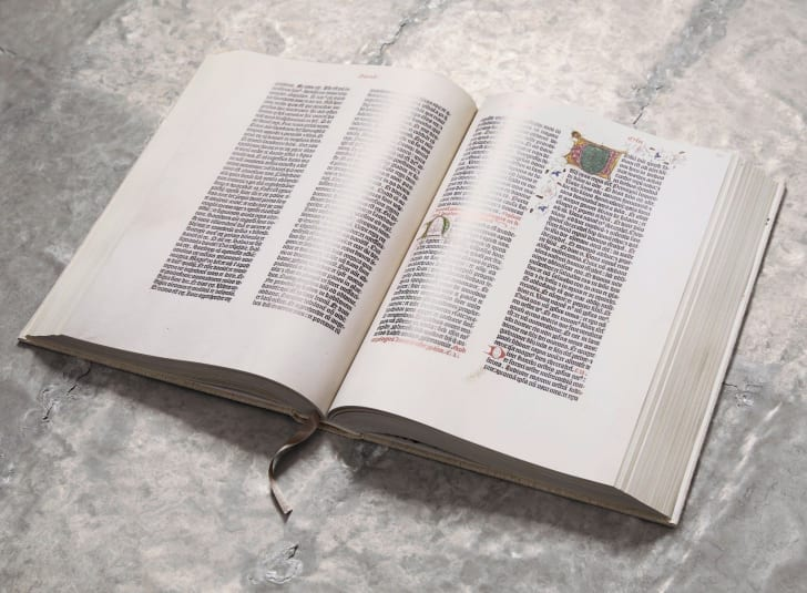 A reprint of the Gutenberg Bible sits open on a table.