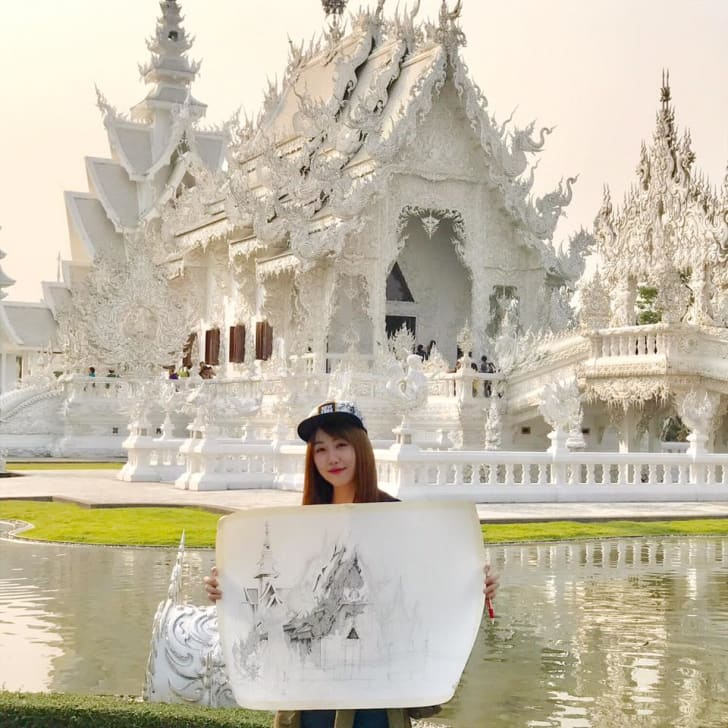 Emi Nakajima holding up her drawing in front of the White Temple