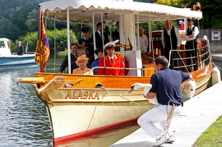 Queen Elizabeth II, accompanied by Swan Marker David Barber (red jacket), watches from the steam launch 'Alaska' as a swan upper places a swan back into the river during a swan upping census on the River Thames on July 20, 2009 near Windsor, England