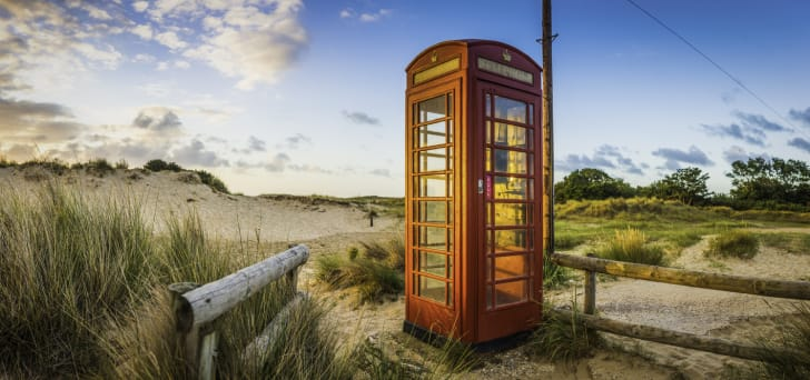 Red telephone box illuminated at sunrise on seaside beach in England