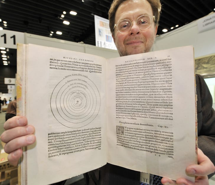 An antique bookseller displays a rare first edition of Nicolaus Copernicus' revolutionary book on the planet system.