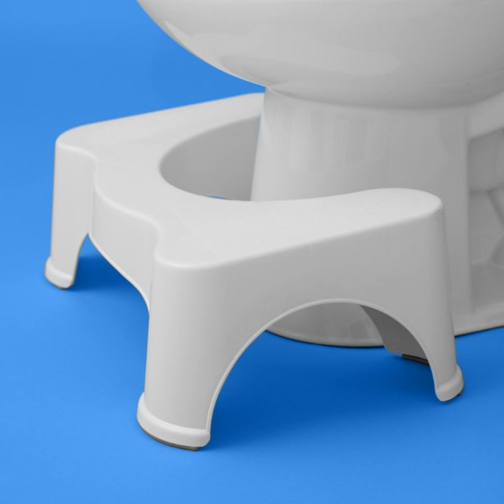 The Squatty Potty sits next to a toilet