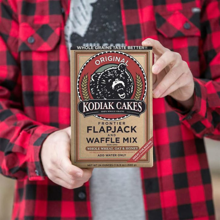 A model holds up a box of Kodiak Cakes pancake mix