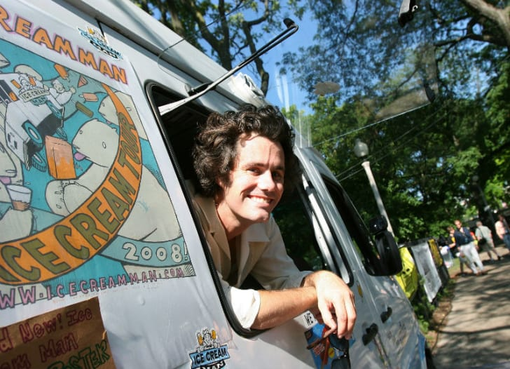 An ice cream truck driver looks out of his window