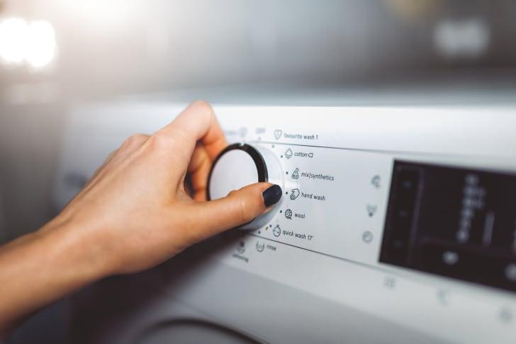 Adjusting settings on a washing machine.