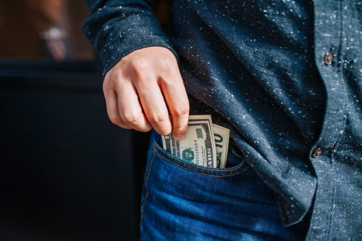 A male hand taking dollar bills out of a pocket
