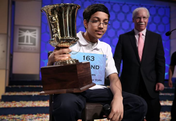 Arvind Mahankali of Bayside Hills, New York holds his trophy as president of the E.W. Scripps Company Rich Boehne looks on after the finals of the 2013 Scripps National Spelling Bee