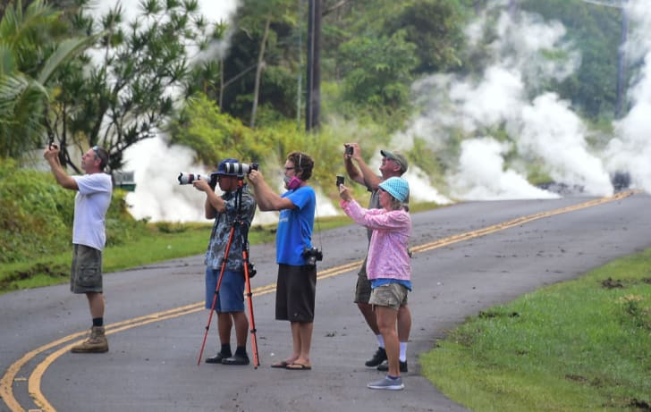 people on road in hawaii taking photos of lava from kilauea volcano