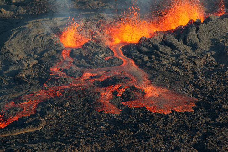 lava from an erupting volcano flows and explodes
