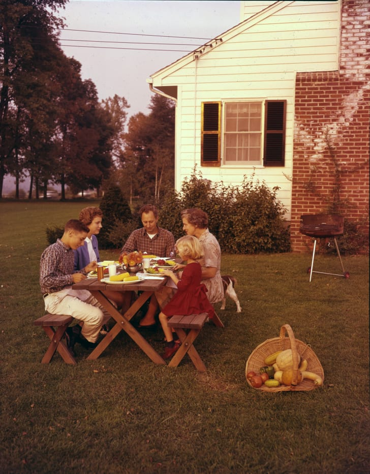 A family eats at a picnic table in the 1960s