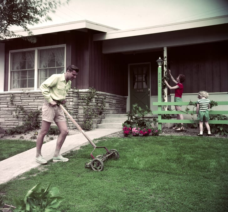 A man mows his lawn in the 1950s
