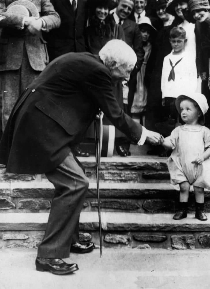 John D. Rockefeller hands a coin to a child