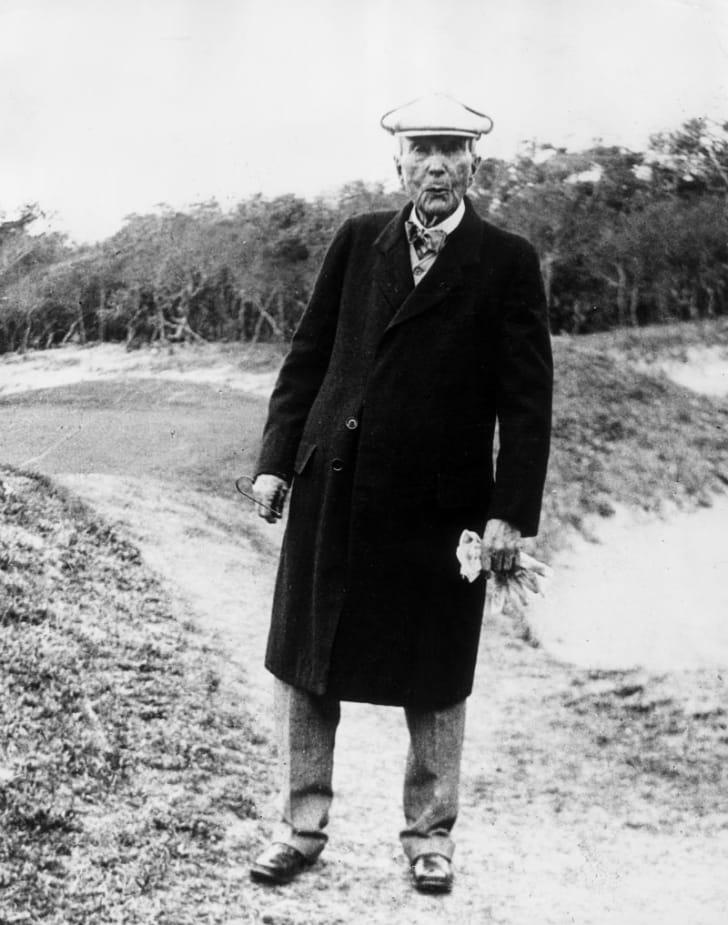 John D. Rockefeller stands in a field