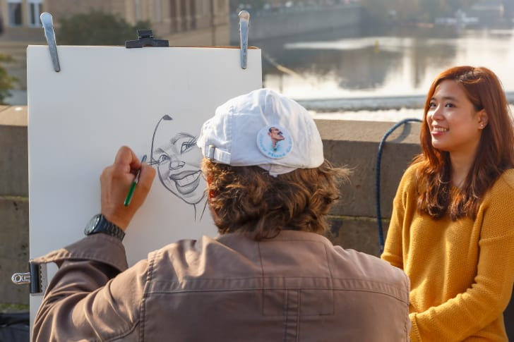 A street artist paints a caricature of a girl in Prague