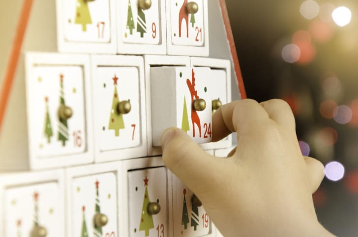 A child pulls a drawer out of an advent calendar.