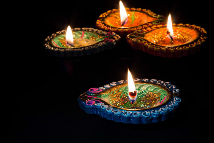 Four burning candles for Diwali.