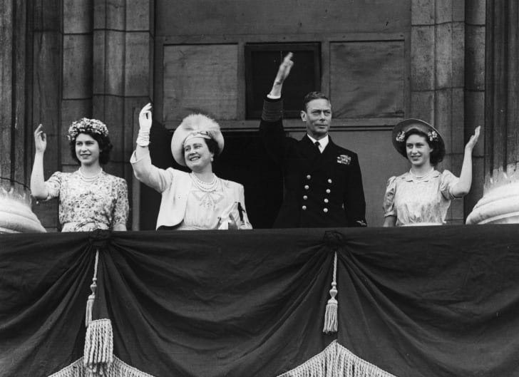 From left to right, Princess Elizabeth, Queen Elizabeth, King George VI, and Princess Margaret Rose wave from the balcony of Buckingham Palace August 15, 1945 on VJ Day in London, England