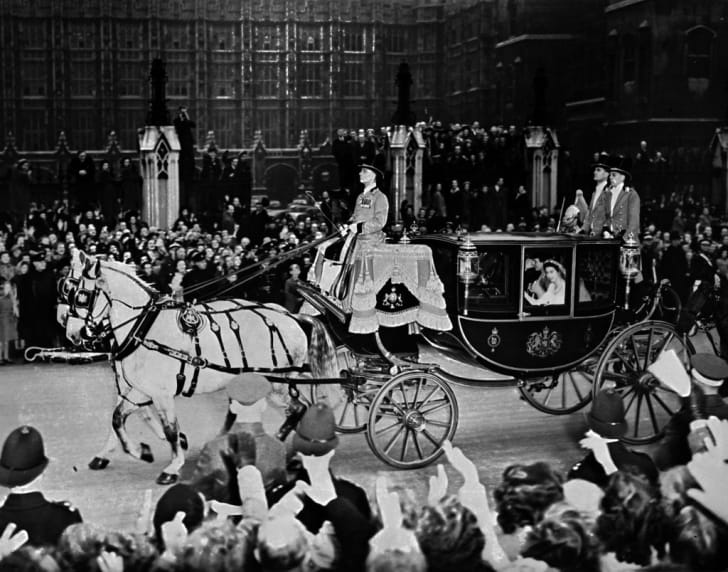 Queen Elizabeth II (in coach) and her husband Prince Philip, Duke of Edinburgh are cheered by the crowd after their wedding ceremony, on November 20, 1947, on their road to Buckingham Palace