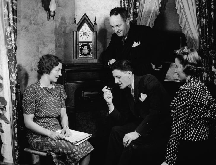 Four men and women gather closely together while listening to their home radio console, 1930s