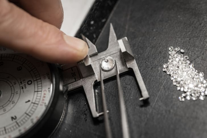 A jeweler measures a diamond