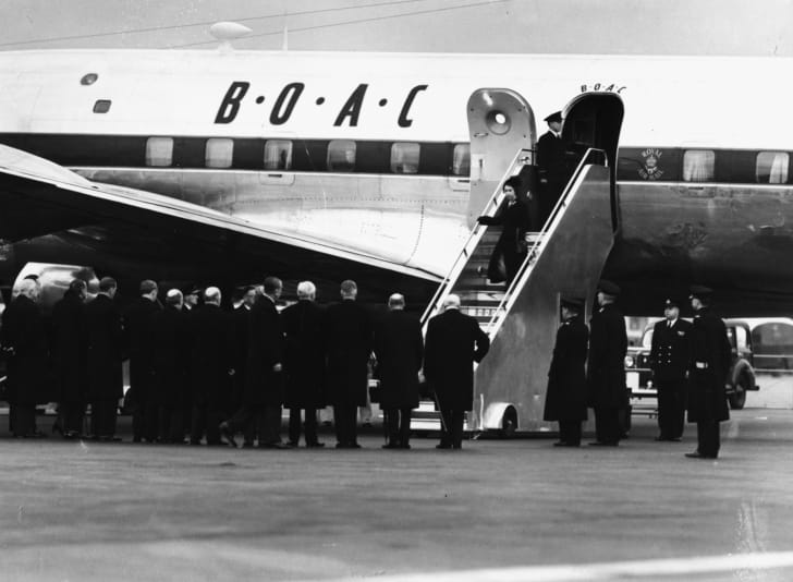 Queen Elizabeth II and Prince Philip, the Duke of Edinburgh, leaving their airplane as they return from Kenya following the death of King George VI in February 1952.