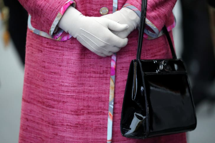 Queen Elizabeth II holds her black Launer handbag during a reception in 2017.