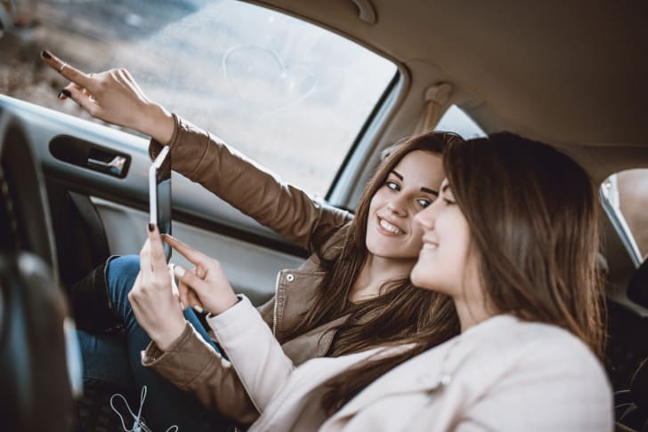 two women in a car looking at a phone