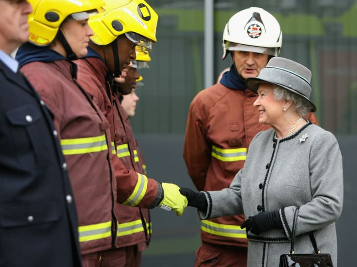 Queen Elizabeth II meets trainee firefighters as she tours the new London Fire Brigade Headquarters at Southwark in February 2008.