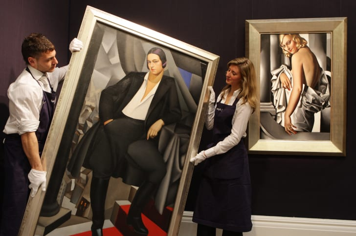 Gallery technicians at Sotheby's auction house lift a painting by Tamara de Lempicka entitled 'Portrait de la Duchesse de la Salle' from 1925, next to another painting by the artist, 'Portrait de Marjorie Ferry' from 1932