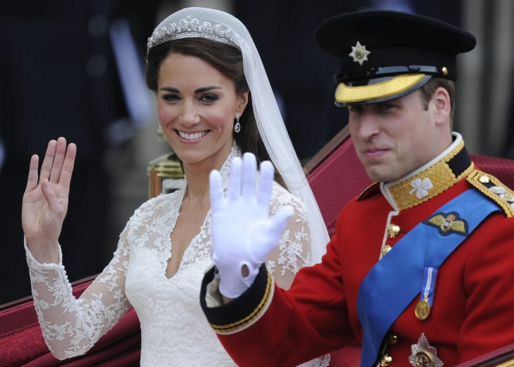 Britain's Prince William and his wife Kate, Duchess of Cambridge, wave as they travel in the 1902 State Landau carriage along the Processional Route to Buckingham Palace, in London, on April 29, 2011