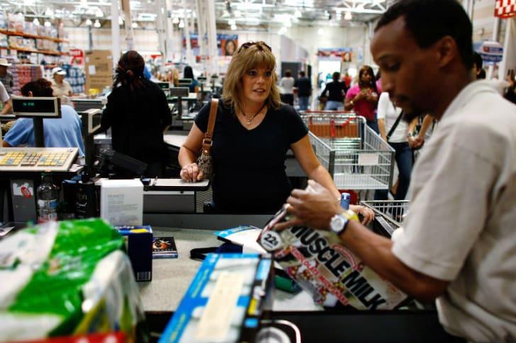 A Costco shopper goes through the checkout lane