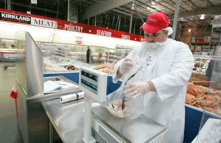 A Costco employee works in food preparation