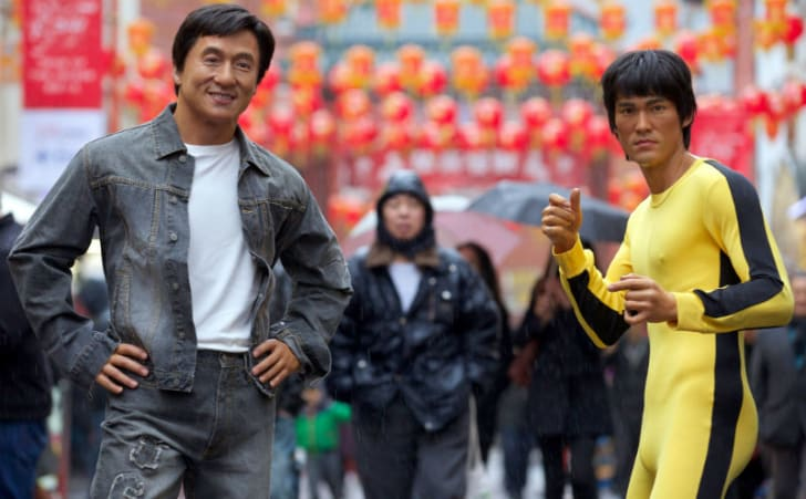 Statues of Jackie Chan and Bruce Lee stand in a public area